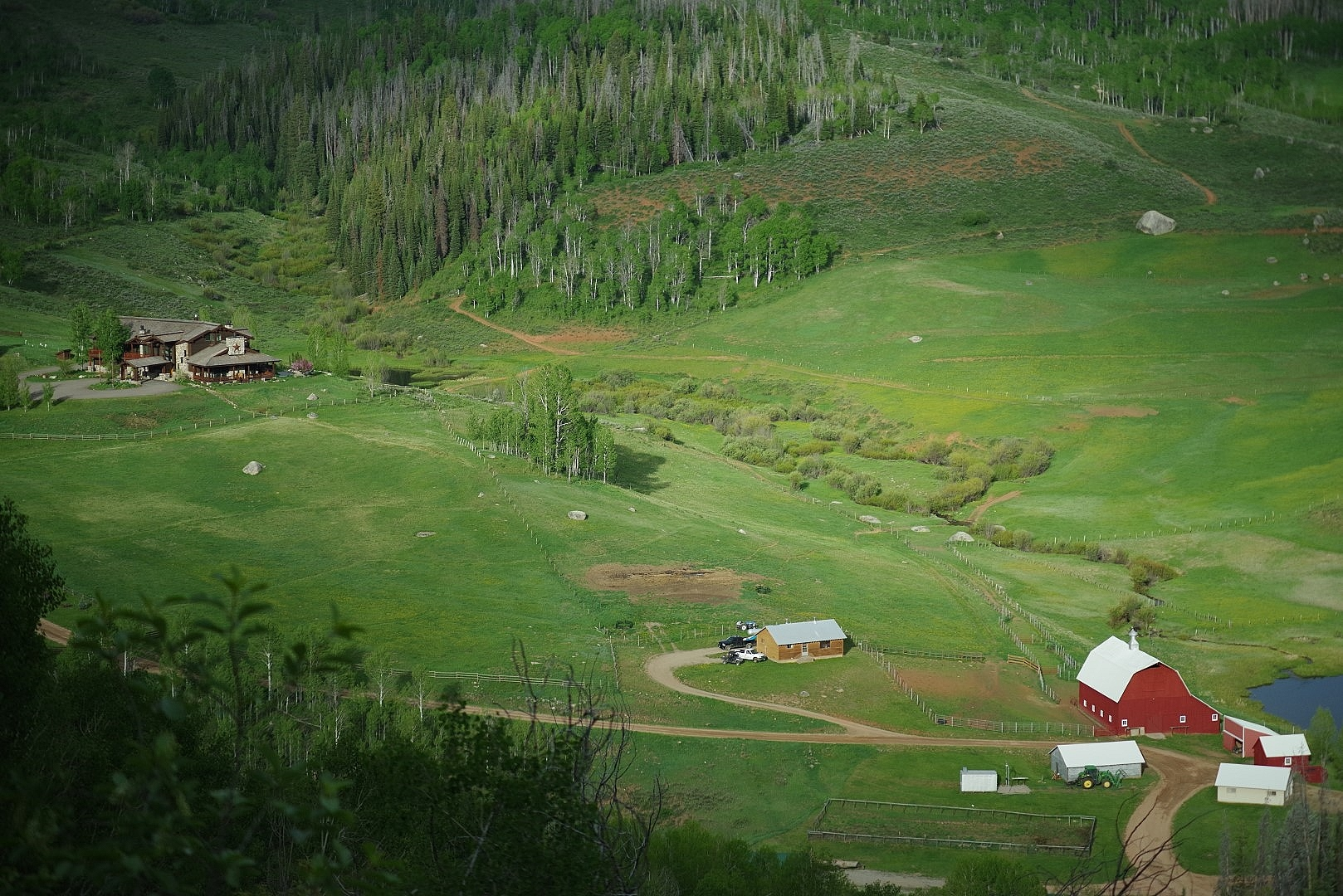 Aerial footage of Big Creek Ranch emcompassing the main house, the red barn, a corner of the pond, employee cabin and shop buildings.