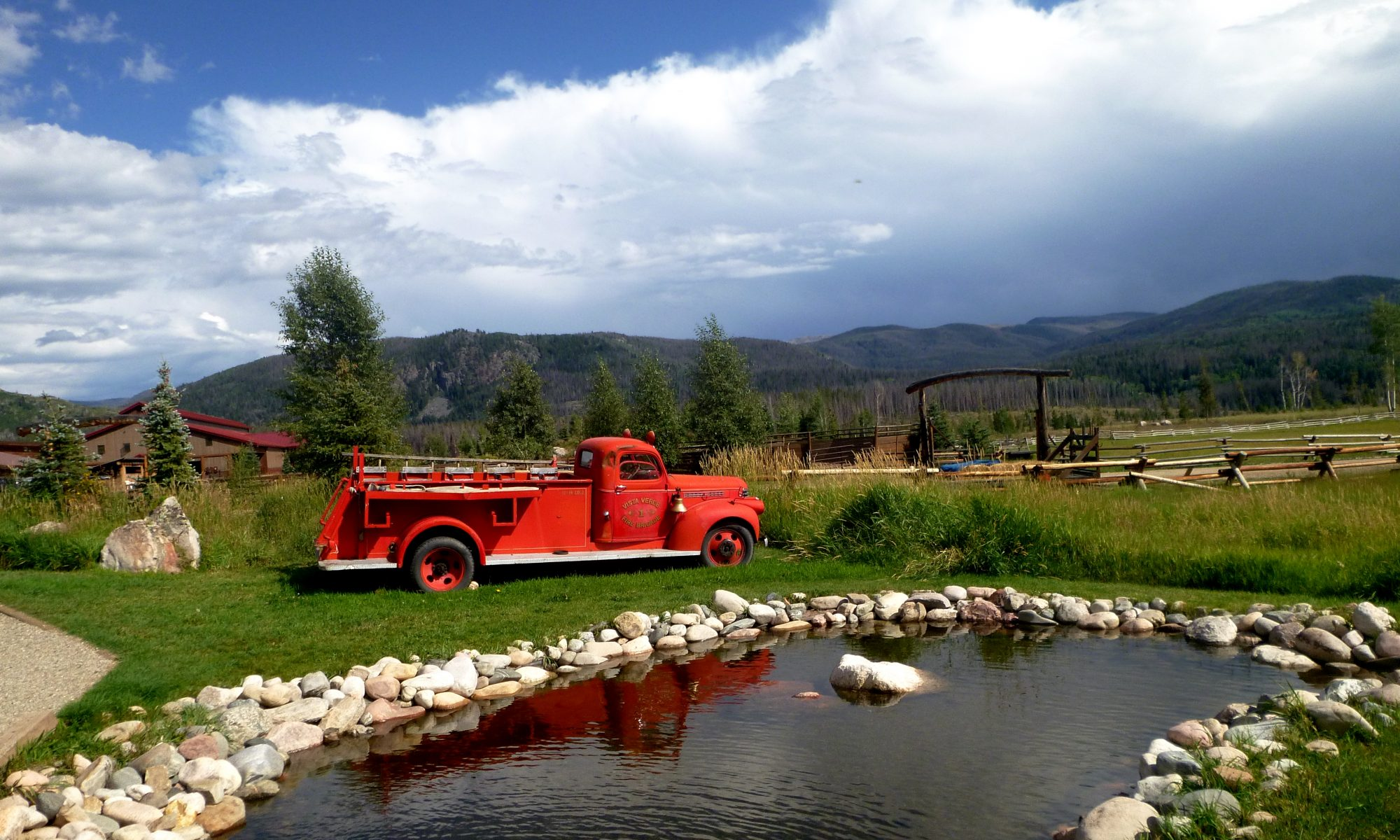 Old fire truck in front of pond